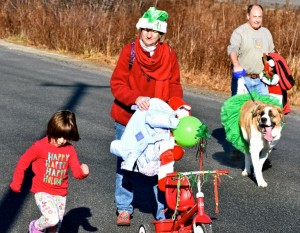 A family clad in festive costumes smiles while walking in Sunday's Santa Run. PHOTO BY TAYLOR VORTHERMS